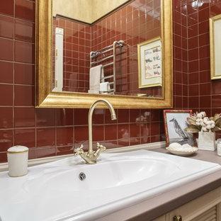 Foto på en mellanstor vintage beige linjär tvättstuga enbart för tvätt, med en enkel diskho, luckor med upphöjd panel, beige skåp, granitbänkskiva, röda väggar, klinkergolv i keramik, en tvättpelare och rött golv