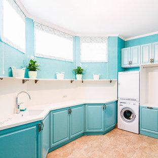 Пример оригинального дизайна: отдельная, угловая прачечная в стиле современная классика с врезной раковиной, фасадами с выступающей филенкой, синими фасадами, синими стенами, с сушильной машиной на стиральной машине, коричневым полом и белой столешницей