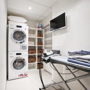 Неиссякаемый источник вдохновения для домашнего уюта: маленькая отдельная прачечная в современном стиле с белыми стенами, полом из керамогранита и вертикальным расположением стиральной и сушильной машин