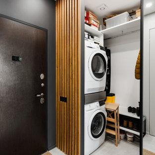 Ispirazione per un ripostiglio-lavanderia design di medie dimensioni con ante in legno chiaro, pareti bianche, pavimento in gres porcellanato, lavatrice e asciugatrice a colonna, pavimento bianco e pareti in legno