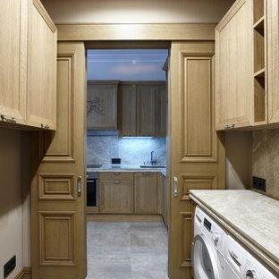 Создайте стильный интерьер: отдельная прачечная в стиле современная классика с бежевыми стенами, со стиральной и сушильной машиной рядом и серым полом - последний тренд