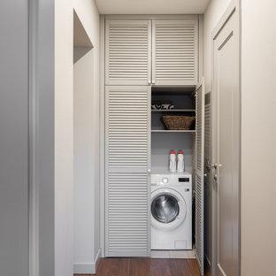 Cette photo montre une buanderie tendance avec un placard, un placard à porte persienne, des portes de placard grises, un sol en bois foncé, le lave-linge et le sèche-linge forment un seul appareil électroménager et un sol marron.