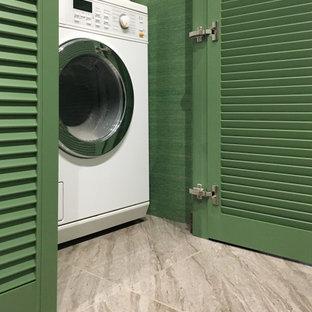 Idéer för en liten modern liten tvättstuga med garderob, med luckor med lamellpanel, gröna skåp, gröna väggar, klinkergolv i porslin och grått golv