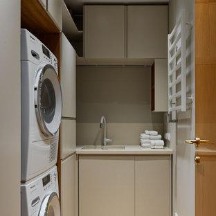 Idéer för funkis l-formade vitt tvättstugor enbart för tvätt, med en undermonterad diskho, släta luckor, beige skåp, en tvättpelare och brunt golv