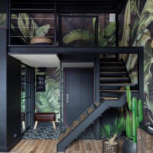 Imagen de entrada industrial, pequeña, con paredes multicolor, suelo de baldosas de cerámica, puerta simple, puerta negra y suelo negro