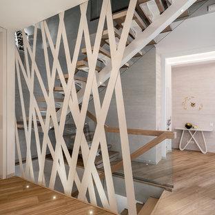 他の地域の広い片開きドアコンテンポラリースタイルのおしゃれな玄関ロビー (ピンクの壁、磁器タイルの床、白いドア、茶色い床) の写真
