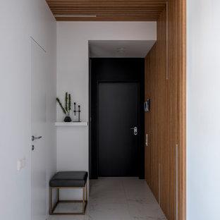 Foto di una porta d'ingresso contemporanea con pareti bianche, una porta singola, una porta nera e pavimento bianco