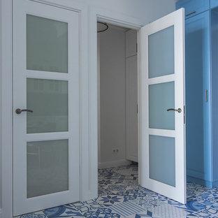 他の地域の小さいビーチスタイルのおしゃれな玄関 (白い壁、磁器タイルの床、青い床) の写真