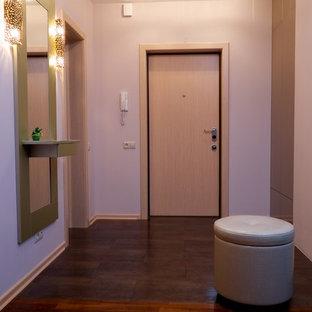 Cette image montre une petit porte d'entrée design avec un mur rose, un sol en carrelage de céramique, une porte simple, une porte en bois clair et un sol violet.