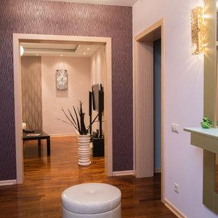 Неиссякаемый источник вдохновения для домашнего уюта: маленькая узкая прихожая в современном стиле с розовыми стенами, полом из керамической плитки, одностворчатой входной дверью, входной дверью из светлого дерева и фиолетовым полом