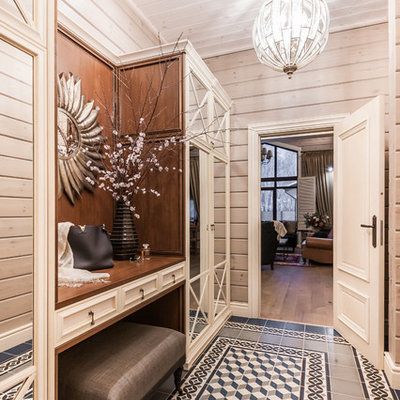 Inspiration for a mid-sized farmhouse ceramic tile, blue floor, wood ceiling and wood wall entryway remodel in Other with beige walls and a brown front door