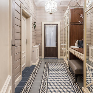 Mid-sized country ceramic tile, blue floor, shiplap ceiling and wood wall entryway photo in Other with beige walls and a glass front door