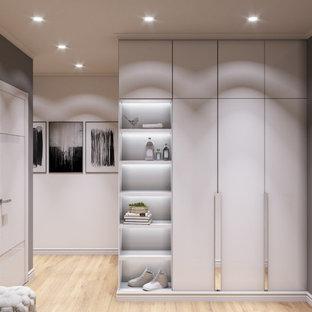 Exempel på en mellanstor modern ingång och ytterdörr, med grå väggar, laminatgolv, en enkeldörr, en vit dörr och beiget golv