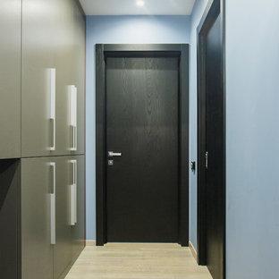 Diseño de hall urbano, pequeño, con paredes azules, suelo laminado, puerta simple, puerta negra y suelo beige