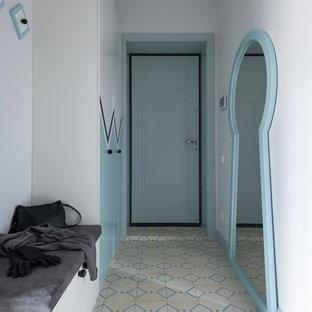 На фото: входная дверь в современном стиле с белыми стенами, одностворчатой входной дверью и разноцветным полом с