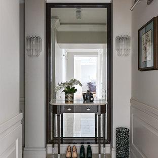 Стильный дизайн: узкая прихожая среднего размера в классическом стиле с бежевыми стенами, полом из керамогранита и коричневым полом - последний тренд