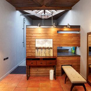 Inspiration pour un grand vestibule design avec un mur gris, un sol en carrelage de porcelaine, une porte simple, une porte métallisée et un sol orange.