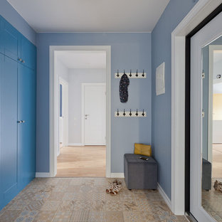 Design ideas for a contemporary hallway in Saint Petersburg with blue walls, porcelain flooring and a white front door.