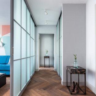 Идея дизайна: узкая прихожая среднего размера в современном стиле с белыми стенами, темным паркетным полом, коричневым полом и правильным освещением