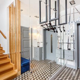 Стильный дизайн: входная дверь в скандинавском стиле с белыми стенами, одностворчатой входной дверью, серой входной дверью и коричневым полом - последний тренд