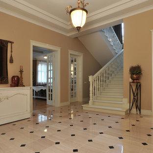 Großer Klassischer Eingang mit brauner Wandfarbe, Keramikboden und beigem Boden in Moskau