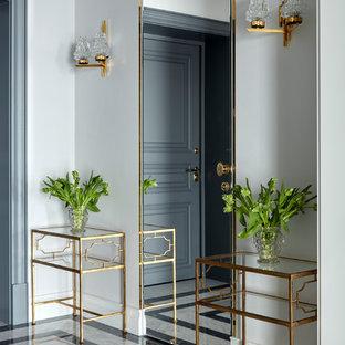 На фото: фойе в стиле современная классика с белыми стенами, мраморным полом, одностворчатой входной дверью и серой входной дверью с