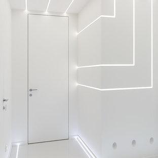 Ispirazione per un piccolo corridoio design con pareti bianche, pavimento in gres porcellanato e pavimento bianco