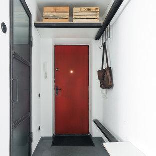 На фото: входные двери в стиле лофт с одностворчатой входной дверью, красной входной дверью, белыми стенами и серым полом