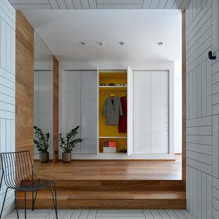 На фото: прихожая среднего размера в скандинавском стиле с белыми стенами, полом из керамической плитки и белым полом с