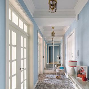 Diseño de hall tradicional, grande, con paredes azules, suelo de baldosas de cerámica, puerta blanca y puerta simple