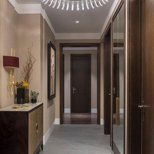 Свежая идея для дизайна: узкая прихожая среднего размера в стиле современная классика с бежевыми стенами, полом из керамогранита, серым полом, одностворчатой входной дверью и входной дверью из темного дерева - отличное фото интерьера