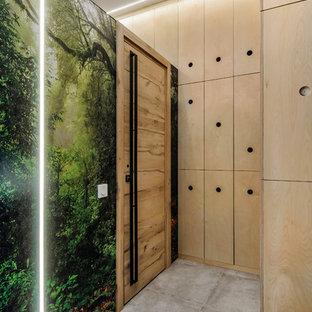 На фото: маленькая узкая прихожая в стиле лофт с полом из керамогранита, серым полом, разноцветными стенами, одностворчатой входной дверью и входной дверью из светлого дерева