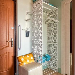 На фото: маленькая входная дверь в современном стиле с одностворчатой входной дверью, входной дверью из дерева среднего тона и коричневым полом с