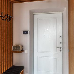 Exemple d'une porte d'entrée tendance avec un mur blanc, une porte simple, une porte blanche et un sol gris.