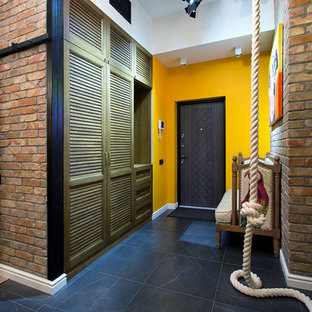 Aménagement d'une porte d'entrée industrielle avec un mur multicolore, une porte simple et une porte noire.