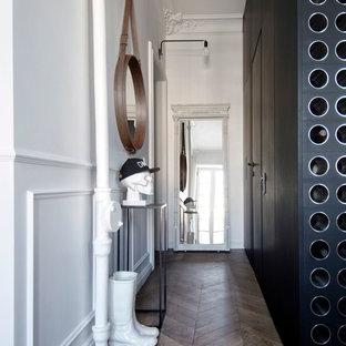 Выдающиеся фото от архитекторов и дизайнеров интерьера: маленькая узкая прихожая в скандинавском стиле с белыми стенами, одностворчатой входной дверью, белой входной дверью и темным паркетным полом