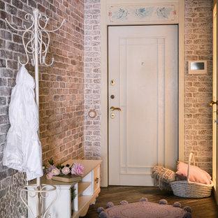 Cette image montre une entrée style shabby chic de taille moyenne avec un couloir, un mur marron, une porte simple, une porte blanche, un sol marron et un mur en parement de brique.