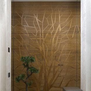 На фото: вестибюль в современном стиле с серебряными стенами, мраморным полом, входной дверью из дерева среднего тона и бежевым полом с