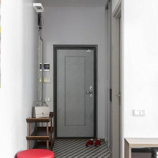 Стильный дизайн: узкая прихожая в современном стиле с полом из керамической плитки, серой входной дверью, одностворчатой входной дверью, белыми стенами и разноцветным полом - последний тренд