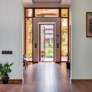 На фото: фойе среднего размера в скандинавском стиле с полом из терракотовой плитки и одностворчатой входной дверью