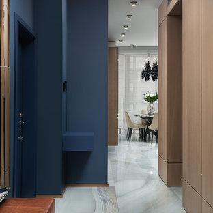 Неиссякаемый источник вдохновения для домашнего уюта: узкая прихожая в современном стиле с синими стенами, одностворчатой входной дверью, синей входной дверью и белым полом