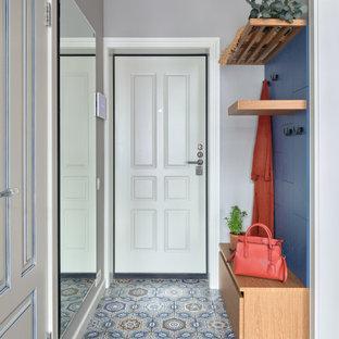 Inredning av en modern ingång och ytterdörr, med grå väggar, en enkeldörr, en vit dörr och blått golv