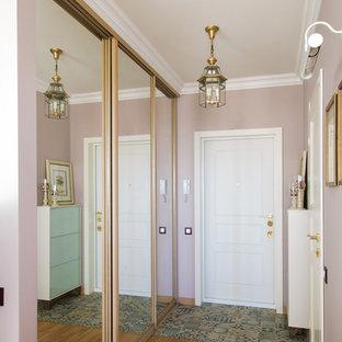 Exemple d'une petit porte d'entrée tendance avec un mur rose, une porte simple, une porte blanche et un sol en bois brun.