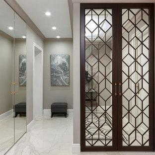 На фото: узкая прихожая в стиле неоклассика (современная классика) с серыми стенами и белым полом с