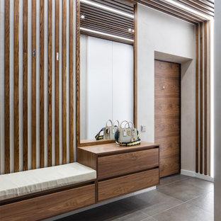 Bild på ett mellanstort funkis kapprum, med klinkergolv i porslin, en enkeldörr, mellanmörk trädörr, vita väggar och grått golv