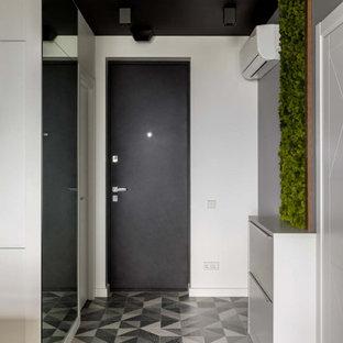 Неиссякаемый источник вдохновения для домашнего уюта: прихожая в скандинавском стиле с серыми стенами, одностворчатой входной дверью, черной входной дверью и серым полом