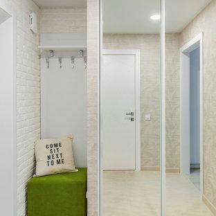 Idee per un piccolo ingresso o corridoio nordico con pareti beige, pavimento in gres porcellanato, pavimento beige e pareti in mattoni