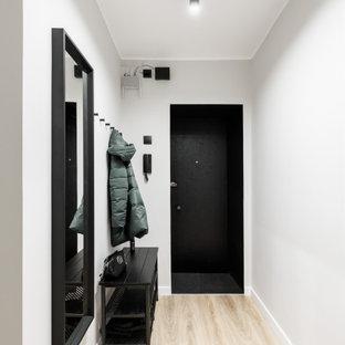 Modern inredning av en liten ingång och ytterdörr, med grå väggar, laminatgolv, en enkeldörr, en svart dörr och brunt golv