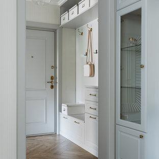 Пример оригинального дизайна: узкая прихожая среднего размера в стиле неоклассика (современная классика) с серыми стенами, полом из керамогранита, одностворчатой входной дверью, серой входной дверью и коричневым полом