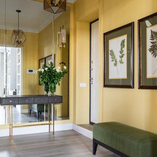 モスクワの中くらいの片開きドアトランジショナルスタイルのおしゃれな玄関ドア (黄色い壁、ラミネートの床、白いドア、ベージュの床) の写真